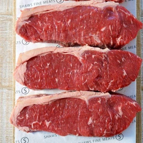 three pieces of beef sirloin steaks on paper and brown cutting board