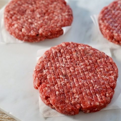 three beef steak and spring onion burgers on white paper located on top of white marble background
