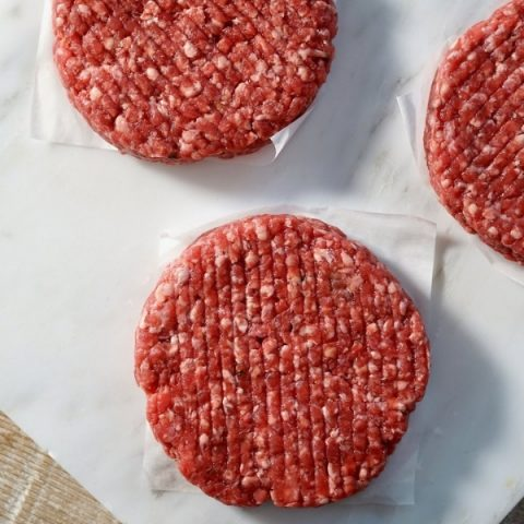 three beef steak burgers on white marble and white paper