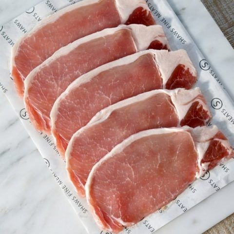 free range unsmoked back bacon slices on paper and white marble