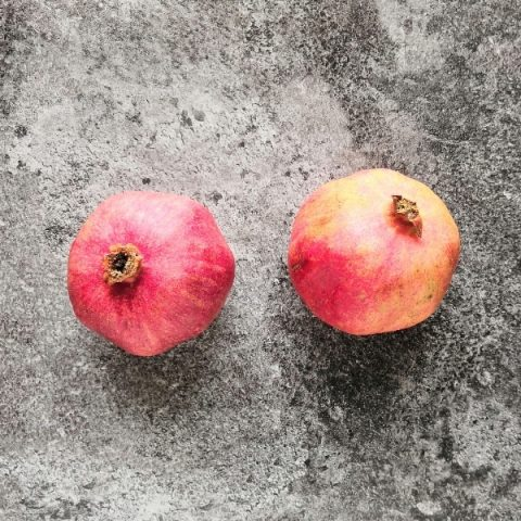 two pomegranates on black marble