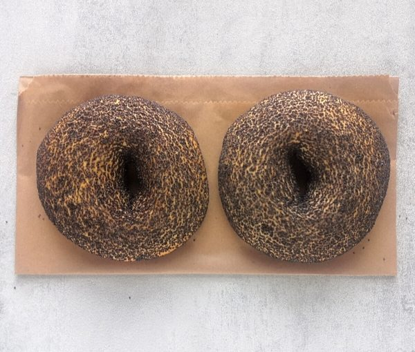 two poppy seeds bagels on brown papar and grey background