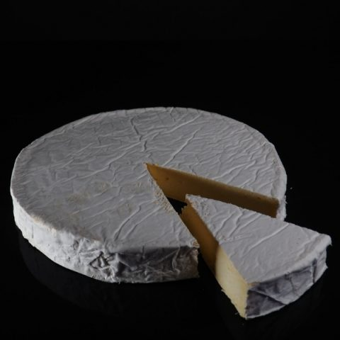 a slice of Clava brie cheese from round block on black background