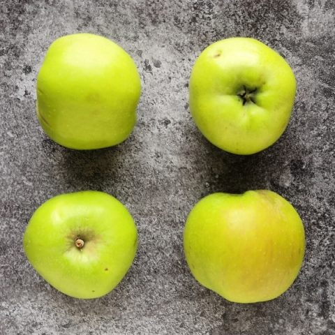 four bramley cooking apples on black marble background