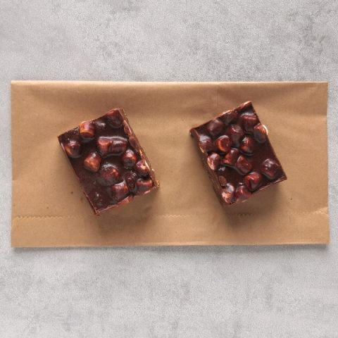 two slices of rocky road on brown paper and grey background