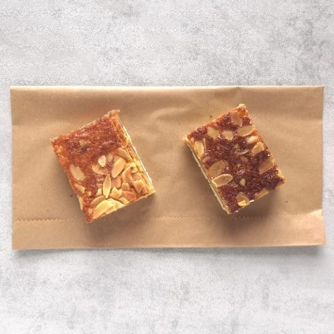 two slices of raspberry and almond on brown paper