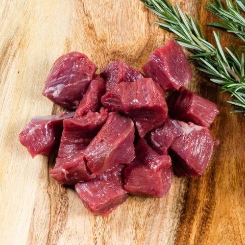 diced lamb lean meat on wood table and fresh rosemary