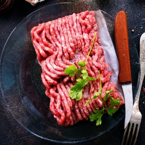 minced lamb with fresh herbs on transparent plate