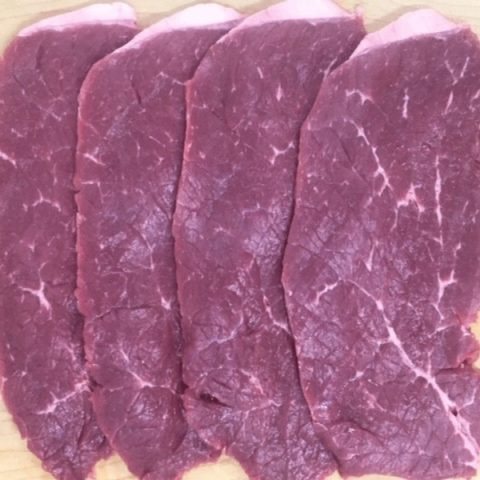 Slices of raw beef minute steaks ready to be cooked