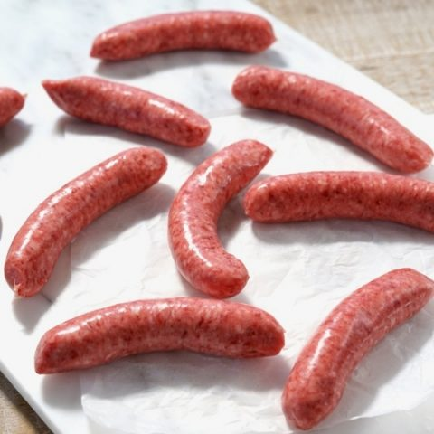 seven beef sausages scattered on white paper and chopping board