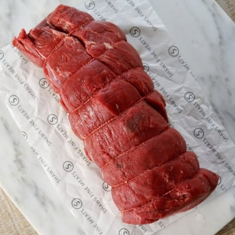 boned and rolled chateaubriand meat on white paper and white marble background