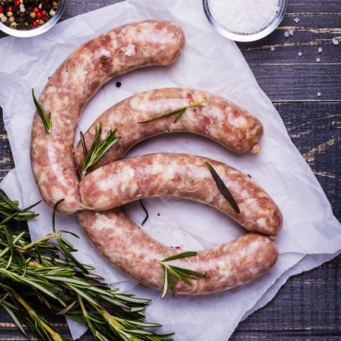 four handmade chorizo sausages on a table with fresh rosemary herb