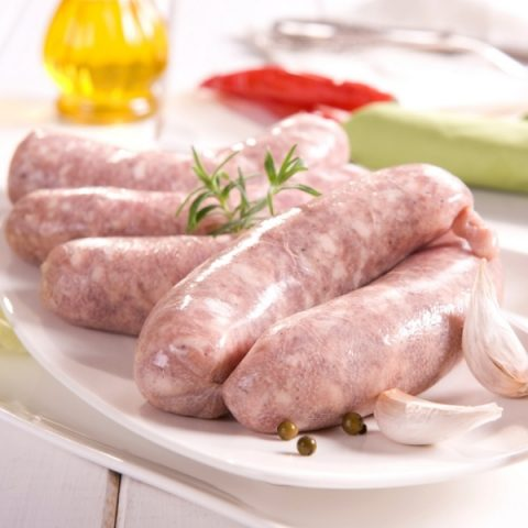 salsiccia pork sausages with garlic bulbs on white plate