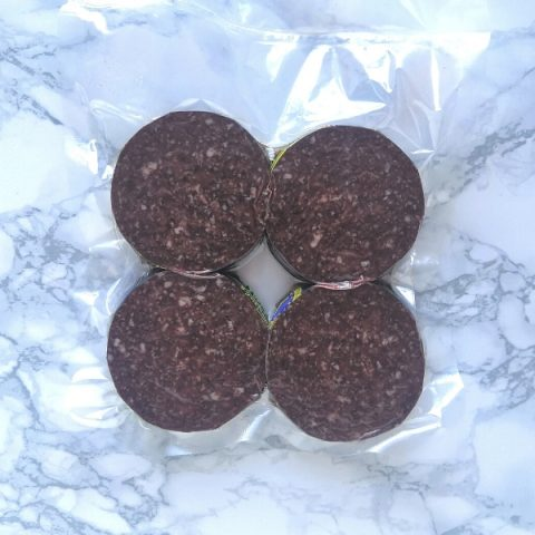 four packed slices of stornoway black pudding on marble
