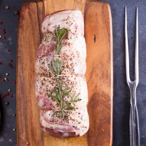 whole leg lamb with rosemary herb and fork on wood board