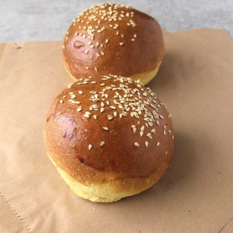 seeded brioche burgers on a brown paper bag