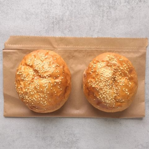 two burger buns with seeds on brown paper