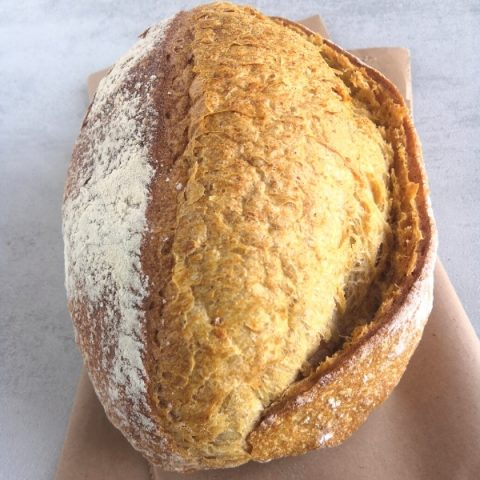 closeup of small sourdough loaf on brown paper and grey background