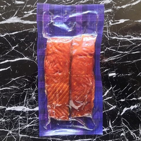 hot smoked salmon packed on a black marble top