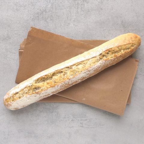 multi seed baguette on brown paper and grey background