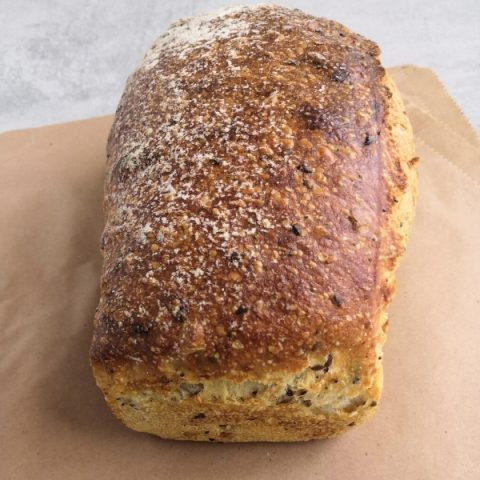 close up of a multi seed tin bread on a brown paper