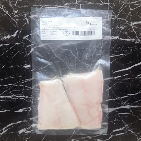 packed hake fillets on black marble background