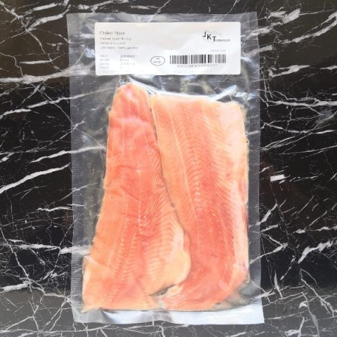 packed rainbow trout fillets on black marble