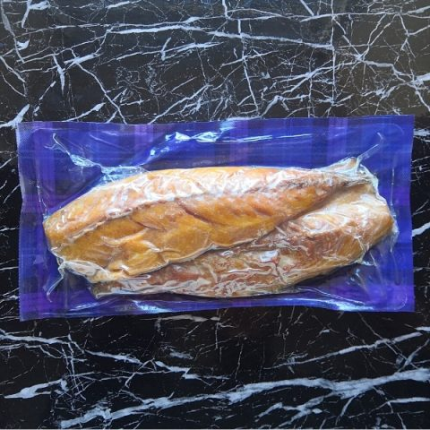 packed smoked mackerel on black marble top