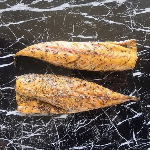 two fillets of peppered mackerel on a black marble top