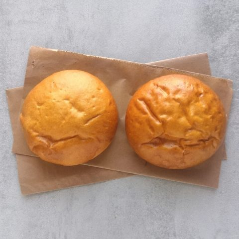 two unseeded, plain burger buns on brown paper and grey background