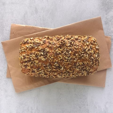 small seeded rye tin bread on brown paper and grey background