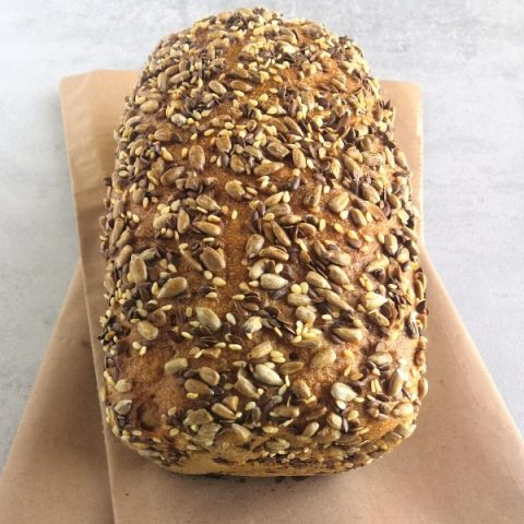 closeup of a small rye tin bread with seeds on brown paper and grey background