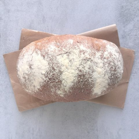 freshly baked small granary tin bread on brown paper and grey background