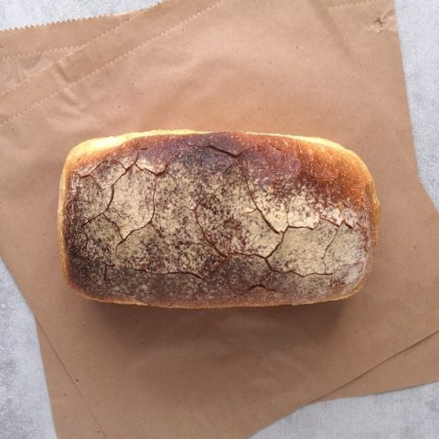 small white tin bread on brown paper and grey background