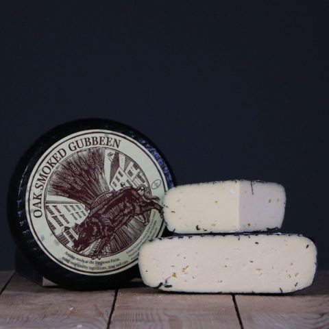 smoked gubbeen cheese on dark background and wood