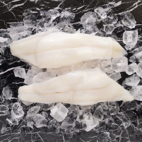Fresh witch sole fillets on ice and on a black marble table