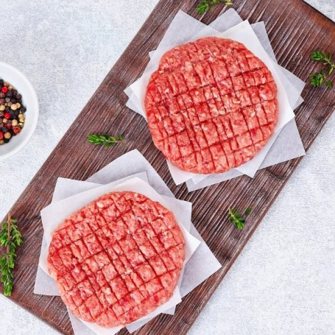 two lamb and mint burgers with fresh herbs on wood cutting board on grey background