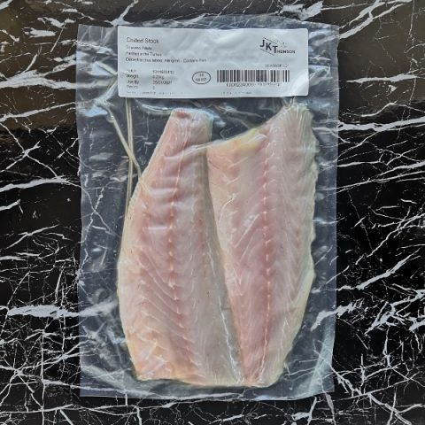 packed seabass fillets on black marble background