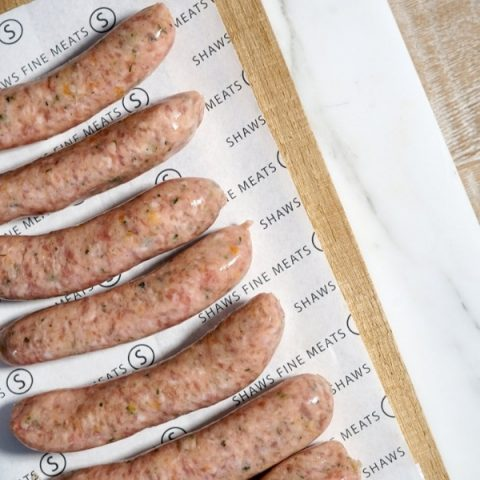 pork, leek and apricot sausages next to one another on paper and brown cutting board