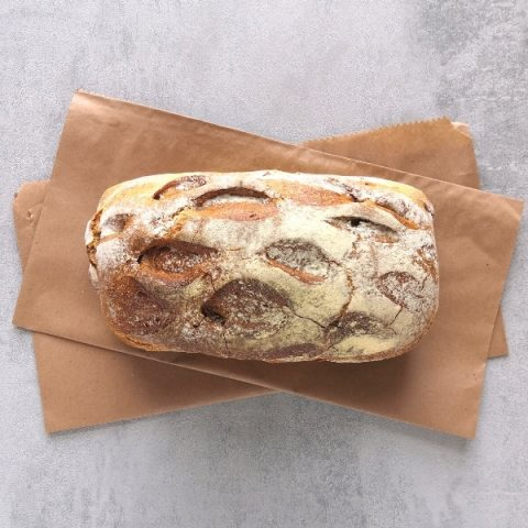 unsliced walnut bread on brown paper and grey background