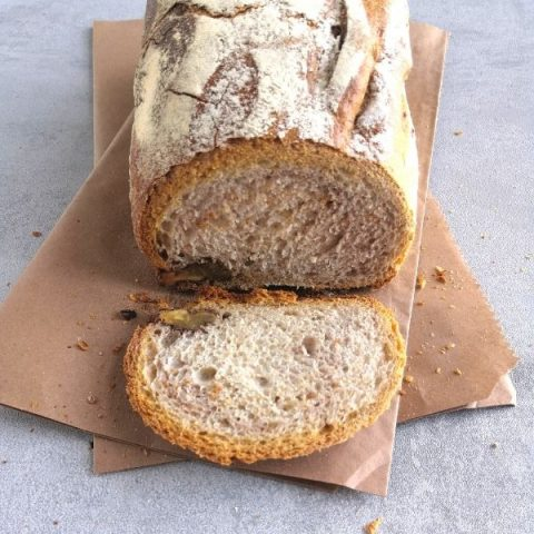 sliced walnut bread on brown paper and grey background