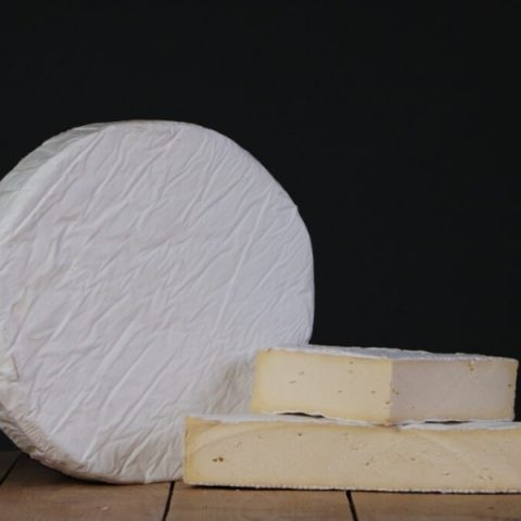Cooleeney cheese round block and slices on wooden table
