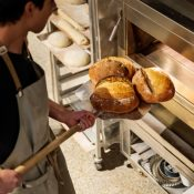 baker taking bread out of the oven