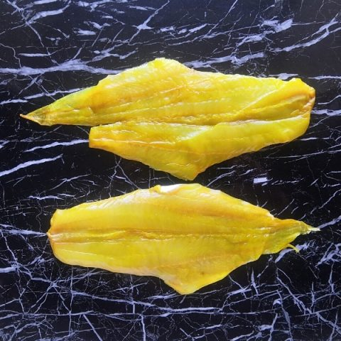 yellow dyed smoked haddock on a black marble table