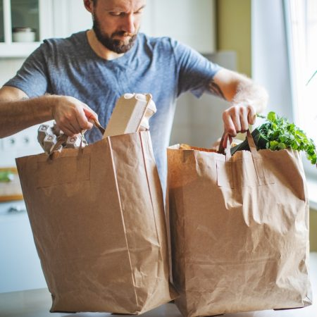 Man in a grey tshirt holding two brown paper bags with groceries