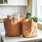 two brown paper bags with groceries on a white table