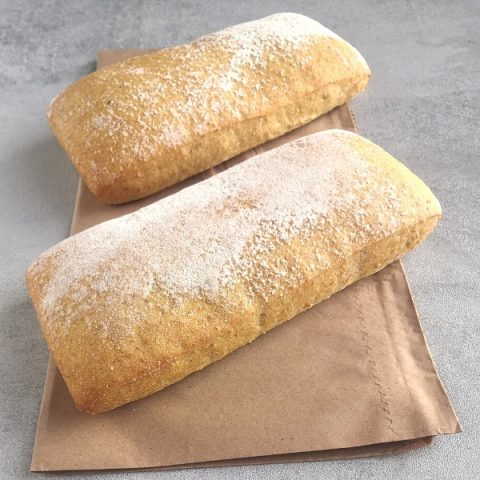two ciabatta country buns on paper on a side