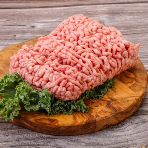 minced pork with curly kale on a wood chopping board